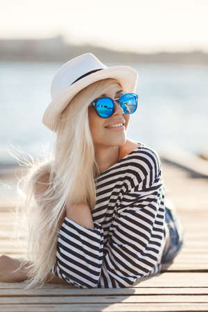 Mooie jonge vrouw met lang blond steil haar, een zonnebril met blauwe glazen, korte broek en een gestreepte shirt zeiler, brengt tijd rusten op een houten pier in de buurt van de zee Stockfoto