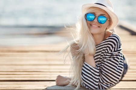 ležérní: Krásná mladá žena s dlouhými blond rovné vlasy, sluneční brýle s modrými brýlemi, šortky a pruhované košile námořník, tráví čas odpočívá na dřevěné molo u moře Reklamní fotografie