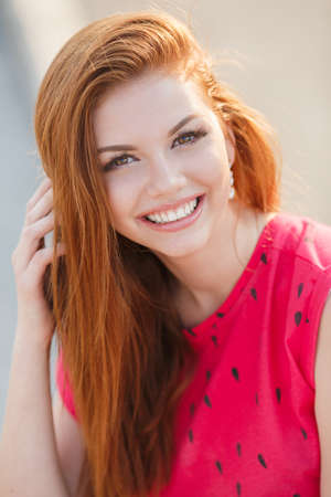 beautiful weather: Summer portrait of beautiful red-haired woman with brown eyes and a sweet smile, dressed in a red blouse sleeveless outdoors on a warm summer day in the city