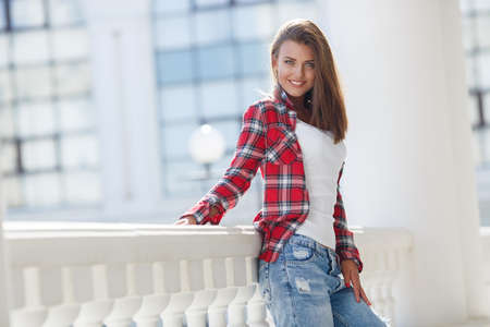 woman fashionable: Portrait Of Young Smiling Beautiful Woman. fashionable casual woman sitting on the floor in city street