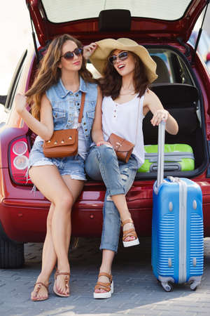 a courtesy: Two cute girlfriends, College girls, brunettes, sun glasses, ladies handbags, courtesy of talking, sitting in the open trunk of the red car next to the blue and green suitcases, waiting for the registration of the aircraft