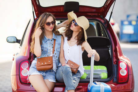 cute girlfriends: Two cute girlfriends, College girls, brunettes, sun glasses, ladies handbags, courtesy of talking, sitting in the open trunk of the red car next to the blue and green suitcases, waiting for the registration of the aircraft