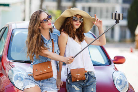cute girlfriends: Two cute girlfriends, College girls, brunettes, sun glasses, ladies handbags in brown color, taking selfies on their mobile phone, posing together, standing near the red car, near the airport, waiting for registration of the aircraft