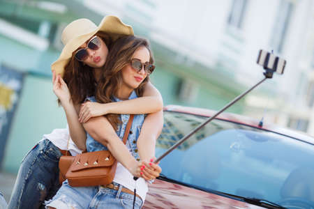 young beautiful friends students taking selfie stick picture together in town happy on sunny day. Closeup of two cheerful friends having fun and taking photos of themselves on smart phone.