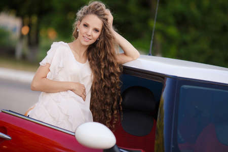 eyes hazel: Cute young pregnant woman, a brunette with long curly hair and hazel eyes, dressed in a thin summer dress in white, beautiful smile, posing for the photographer standing near his favorite red car in the summer outdoors near the Park Stock Photo