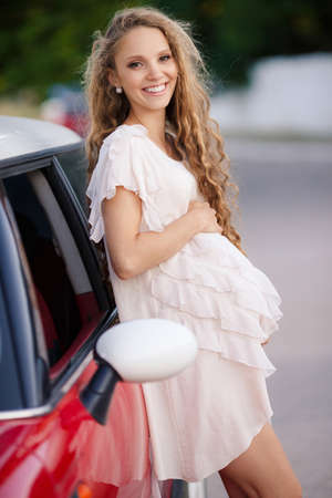 hazel eyes: Cute young pregnant woman, a brunette with long curly hair and hazel eyes, dressed in a thin summer dress in white, beautiful smile, posing for the photographer standing near his favorite red car in the summer outdoors near the Park Stock Photo