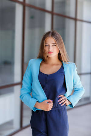 gray eyes: Morning portrait of a business lady, near the office.Portrait of a beautiful long-haired brunette with gray eyes dressed in a blue jacket, light makeup, brooding eyes, standing on the street near his bright office with large Windows during the break Stock Photo