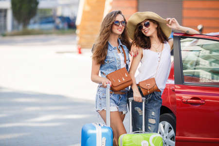 urban travel: Two young beautiful girlfriend, a brunette with long hair, wearing sun glasses, with fashionable handbags brown, standing near a red car with blue and green suitcases, discussing the delights of the upcoming trip. Stock Photo
