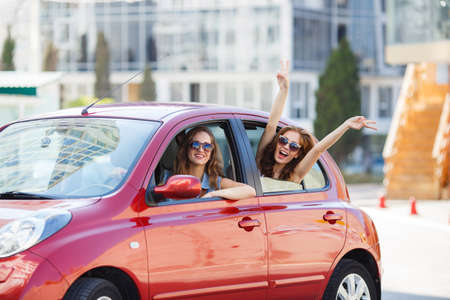 Two happy girlfriends are traveling in the car, Two beautiful young women, brunettes in dark sunglasses, lovely smiling, travel together in the red midget car during summer holiday on the cities of Europe. Stok Fotoğraf
