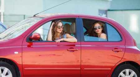 midget: Two happy girlfriends are traveling in the car, Two beautiful young women, brunettes in dark sunglasses, lovely smiling, travel together in the red midget car during summer holiday on the cities of Europe. Stock Photo