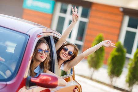 gente feliz: Dos novias felices est�n viajando en el coche, dos bellas mujeres j�venes, morenas en gafas de sol oscuras, encantadora sonriente, viajan juntos en el coche enana roja durante las vacaciones de verano en las ciudades de Europa.