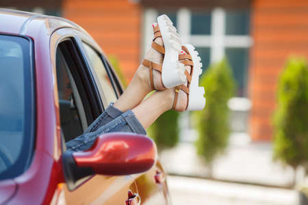 legs open: Day dreaming in car. Close-up of young woman holding legs out of the window while sitting inside the car. female legs dangling from the open car window in the shales