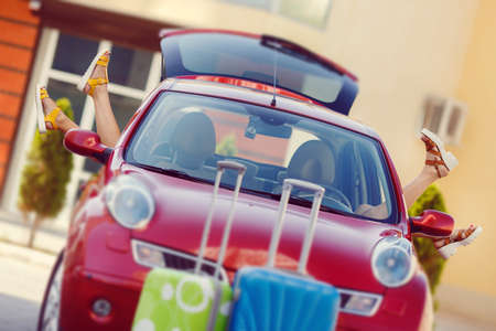 overburden: car with luggage bags and travel suitcases before the family vacation. Car trip. summer holidays. car leaving for the travel. Summer holidays concept
