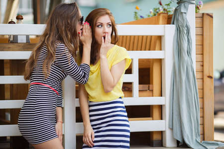 gossip: Two cute women, brunettes with long hair, dressed in a striped summer dress and a striped skirt and a yellow t-shirt, a good friend, share secrets with each other, standing on the street, summer holidays and vacation concept - girls share gossip Stock Photo