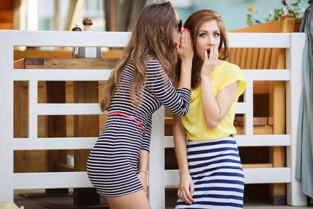 chismes: Dos mujeres lindas, morenas con el pelo largo, vestido con un vestido de verano de rayas y una falda a rayas y una camiseta amarilla, un buen amigo, comparte secretos con los dem�s, de pie en la calle, las vacaciones de verano y concepto de vacaciones - chicas comparten chismes