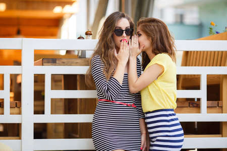 secret: Two cute women, brunettes with long hair, dressed in a striped summer dress and a striped skirt and a yellow t-shirt, a good friend, share secrets with each other, standing on the street, summer holidays and vacation concept - girls share gossip Stock Photo