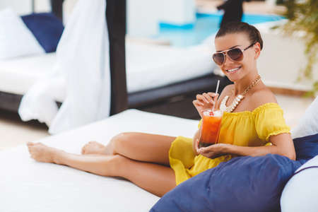 cocktail dress: Young beautiful woman enjoying summer vacation on a tropical resort, a beautiful young woman in a yellow dress, holding a glass of cocktail while relaxing on a white lounger by the pool, beautiful, sexy woman drinking cocktail