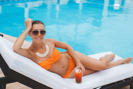 tans: Sexy young woman tans on the sun lounger, beautiful girl in orange bikini with a cocktail lying next to the pool, photos from the top position, the woman sunbathes in bikini on a tropical resort, a beautiful woman lying on a lounger by blue water