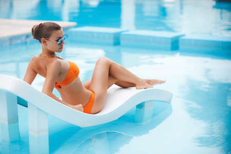 Sexy young woman tans on the sun lounger, beautiful girl in orange bikini with a cocktail lying next to the pool, photos from the top position, the woman sunbathes in bikini on a tropical resort, a beautiful woman lying on a lounger by blue water