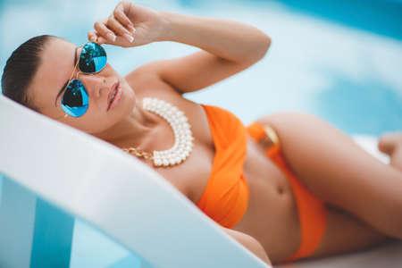 niñas en bikini: Broncea Mujer joven atractiva en la tumbona, hermosa chica en bikini naranja con un cóctel tumbado junto a la piscina, fotos de la primera posición, la mujer toma el sol en bikini en un resort tropical, una hermosa mujer tumbada en una hamaca por el agua azul