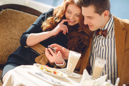 A nice man, a beautiful brunette with brown eyes, light brown suit and bow tie and red-haired young woman with brown eyes, wearing a black dress, spend time together over a cup of coffee in summer cafe in the open air, looking at photos on mobile phone Standard-Bild