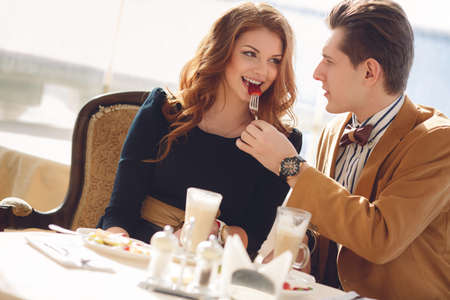 The man, a beautiful brunette with brown eyes, light brown suit and bow tie and red-haired young woman with brown eyes, wearing a black dress, spend time together over a cup of coffee in summer cafe outdoors.