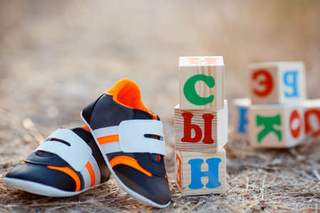 wooden blocks: Childrens shoes and the word son, paved with wooden cubes, Bright little sneakers, orange, black and white, standing on the ground beside a pyramid of wooden blocks with letters, from which a pregnant woman laid out the word SON. Stock Photo