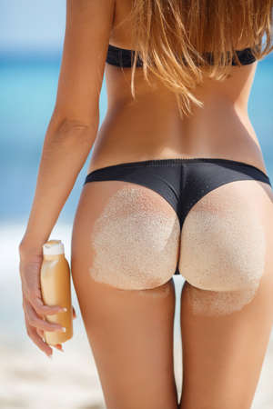 nude butt: Sexy sandy woman buttocks on tropical beach background near ocean. close up outdoor shot of young woman in white bikini, sunbathing at sea shore. Black bikini on ocean background Stock Photo