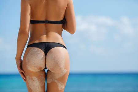 Sexy Frau Gesäß auf sandigen tropischen Strand Hintergrund in der Nähe von Meer. close up draußen Schuss junge Frau im weißen Bikini, Sonnenbaden am Meer. Schwarzen Bikini auf Ozean Hintergrund