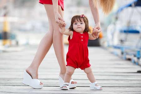 美しい母親は、最初のステップ、彼女の小さな赤ちゃん女の子娘と桟橋に歩いています。最初の手順を実行します。母と子。母は歩くことを学習に