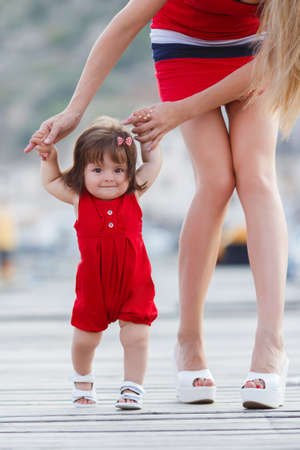 beautiful mother is walking on the pier with her little baby girl daughter with first steps. First steps. mother and child. mother holding child's hands supporting by learning to walk Foto de archivo