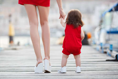 beautiful mother is walking on the pier with her little baby girl daughter with first steps. First steps. mother and child. mother holding childs hands supporting by learning to walk