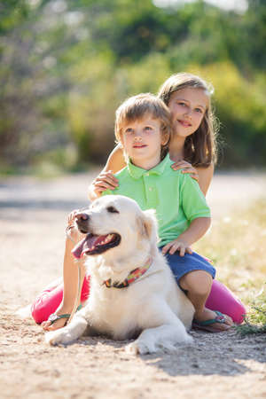 girl sit: two children with dog on nature. girl and boy with labrador retriever in summer park. children have fun with dog. outdoor portrait