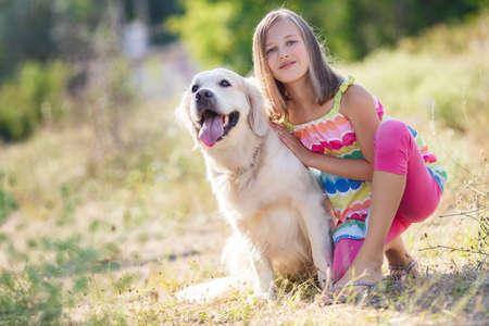 Portret van een vrouw met haar mooie hond buiten. Schattig klein meisje knuffelen golden retriever. Jong meisje met golden retriever weglopen in zon