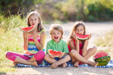 Three happy smiling child eating watermelon in park.Two girls and a little boy, two sisters and a brother, happy family sitting on the ground, barefoot, in a green summer park happy to eat a ripe red watermelon and looking at the camera