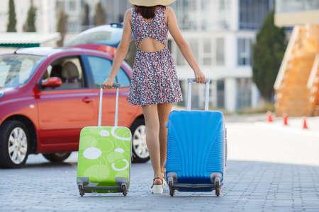 女性は、道を歩いて、スーツケースと一緒に旅行します。若いの幸せな女、軽いサマードレスに、大きな麦藁帽子、髪の長いブルネットの車輪の上 写真素材