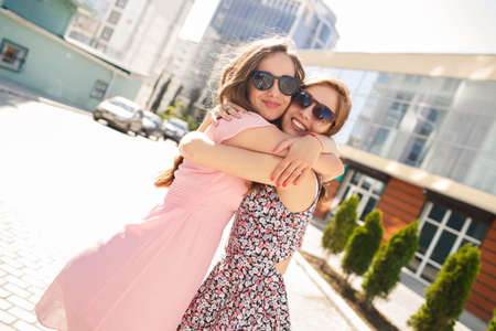 friend hug: two friends outdoors. two girls having fun. Smiling women outdoor. two beautiful young women having fun in the city. Two women friends laughing with a perfect white teeth