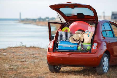 maleta: Maletas y bolsas en maletero del coche listo para ir de vacaciones, el coche rojo con un baúl abierto cargado a capacidad con cosas para relajarse, en la playa cerca del mar, un viaje al campo para una familia feliz