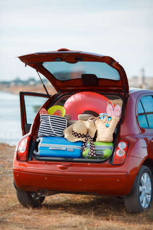 overburden: Suitcases and bags in trunk of car ready to go on vacation, the red car with an open trunk loaded to capacity with things to relax, on the beach near the sea, a trip into the countryside for a happy family