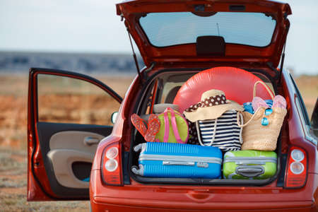 big family: Suitcases and bags in trunk of car ready to go on vacation, the red car with an open trunk loaded to capacity with things to relax, on the beach near the sea, a trip into the countryside for a happy family