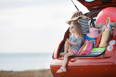 A little girl, a brunette with long curly hair, dressed in a striped sailor shirt, dark sun glasses, and a journey to the sea, sits in the trunk of the red car with clothes, suitcases and bags Standard-Bild