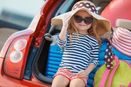 in need of space: A little girl, a brunette with long curly hair, dressed in a striped sailor shirt, dark sun glasses, and a journey to the sea, sits in the trunk of the red car with clothes, suitcases and bags Stock Photo