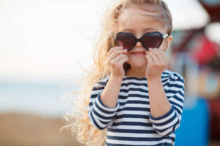 seaside: happy little girl at the seaside in the summer.Adorable little girl at beach during summer vacation. Happy baby with sunglasses by the sea