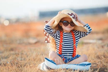 Gelukkig meisje in een grote hoed, Mooie jonge dame, een brunette met lang krullend haar, gekleed in een gestreepte zeiler shirt en rode bretels, het dragen van donkere zonnebril, zittend op een rotsachtige strand in een grote strooien hoed. Stockfoto