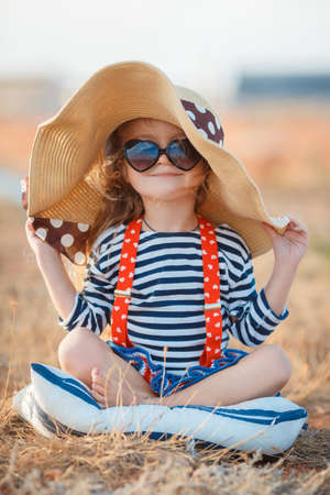 Happy little girl in a large hat, Beautiful young lady, a brunette with long curly hair, dressed in a striped sailor shirt and red suspenders, wearing dark sunglasses, sitting on a rocky beach in a big straw hat. Standard-Bild