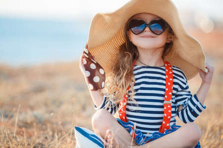 Happy little girl in a large hat, Beautiful young lady, a brunette with long curly hair, dressed in a striped sailor shirt and red suspenders, wearing dark sunglasses, sitting on a rocky beach in a big straw hat. Stockfoto