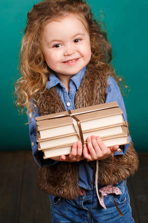 schoolgirl: Studio portrait of a little girl on a turquoise background with a pile of books in her arms, the brunette with long curly hair and brown eyes, wearing a blue shirt and fur vest, funny smile, preparation for school