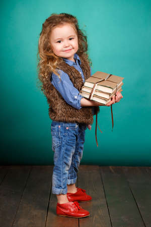young schoolgirl: Studio portrait of a little girl on a turquoise background with a pile of books in her arms, the brunette with long curly hair and brown eyes, wearing a blue shirt and fur vest, funny smile, preparation for school