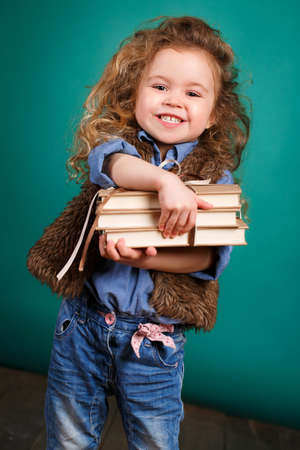 achiever: Little girl with books. Child studying. Schoolchild. Schoolgirl. studio portrait. school preparation. baby holding bunch of books. education. pupil.