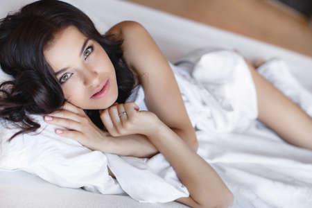belle brune: Portrait de la belle femme de d�tente dans son lit � la maison, brune aux cheveux longs et les yeux bruns, sourire attrayant, �treignant l'oreiller couch� sur blanc Portrait de lit de jeune femme heureuse de se r�veiller dans son lit t�t le matin